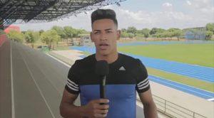 Deluan fala no microfone com pista de atletismo ao fundo