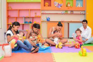 Mães brincando com seus filhos em brinquedoteca e um pai com o filho no mesmo ambiente