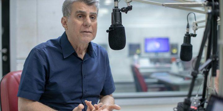 Romero Jucá falando no microfone em estúdio de rádio. Falou sobre a vida
