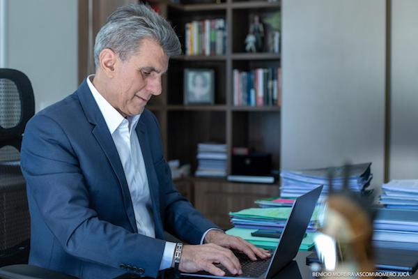 Jucá olhando para computador escreve artigo sobre o Orçamento da União e explica que ajudou a incluir Roraima como prioridade.