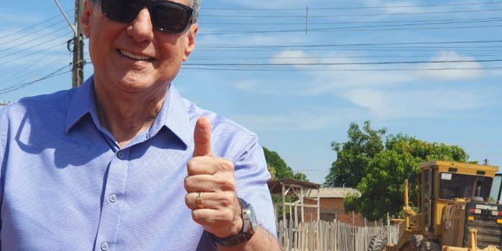 Romero Jucá faz sinal de legal enquanto visita obra de asfalto em Boa Vista. Ele fala da importância de trabalhar para que Roraima seja atendida no Orçamento da União