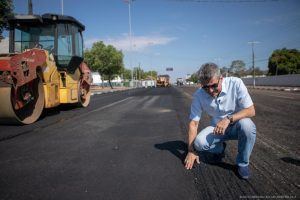 Jucá agachado e olhando para rua sendo asfaltada em Boa Vista