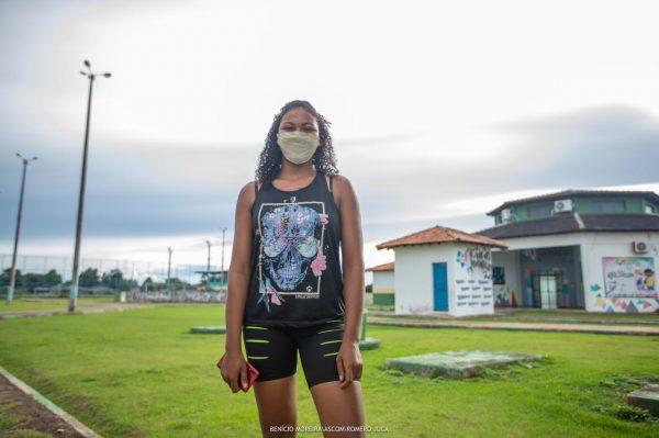 Jéssica de camiseta e short pretos em frente à Estação da Juventude