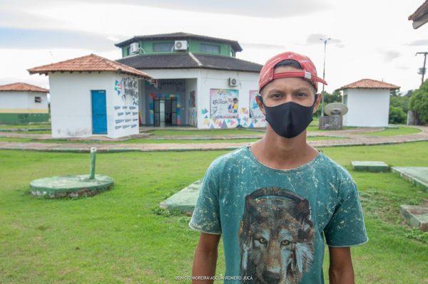 Kauan Alves em pé na frente da Estação da Juventude. Ele está de camisa verde, máscara e Boné