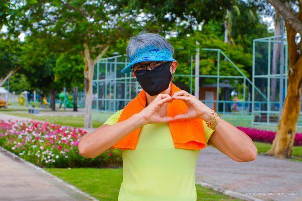Imagem de uma senhora fazendo um sinal de coração com as mãos em praça do senador da praça