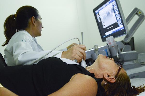 Profissional de saúde, olha para a tela do computador, onde aparece a imagem da garganta da paciente examinada em aparelho de ultrassonografia do centro de prevenção ao câncer de Boa Vista