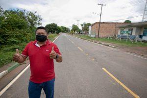 Francival Cavalcante faz sinal de positivo em rua asfaltada por Senador de Roraima
