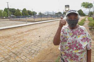 Ilca Ferreira faz sinal de positivo em frente da praça que está sendo construída