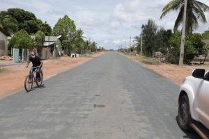 Imagem de rua asfaltada tem carro e homem pedalando. Asfalto é resultado do trabalho de senador em Normandia