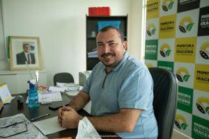 Jairo Ribeiro sorri sentado em seu gabinete na Prefeitura com foto de Jucá no fundo