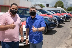 Juliano Torquato e Jucá fazem sinal de positivo com veículos ao fundo