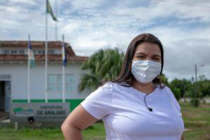Núbia Oliveira de camisa branca em frente da Prefeitura de Amajari