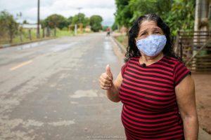 Ilda Mota faz sinal de positivo na rua em que mora. Lugar asfaltado é fruto da parceria com Iracema de Jucá