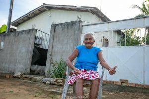 Leonice da Silva sentada na frente da casa dela. Trabalho de senador em Mucajaí asfaltou diversas ruas