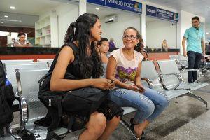 Pessoas sorrindo sentadas no terminal Luiz Canuto e ao fundo os box para comercialização de alimentos