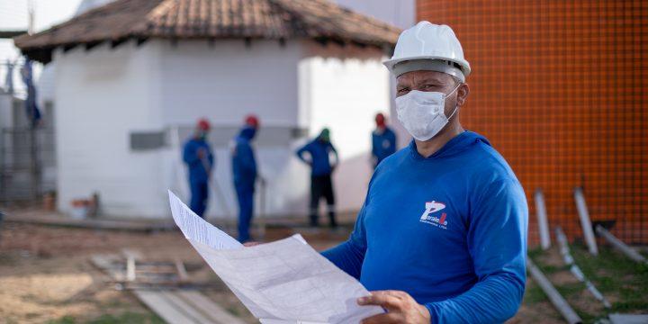 Magno Félix segura uma planta baixa em obra. Ele é um dos beneficiados com a geração de empregos