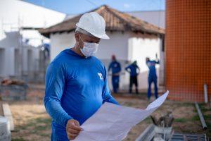 Magno Félix olha uma planta baixa. Mais empregos são gerados com as obras com recursos de Jucá