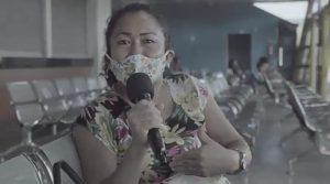Mara Neves sentada em terminal com o microfone na mão