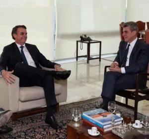 Romero Jucá e Bolsonaro conversam sentados cada um em um sofá em Brasília