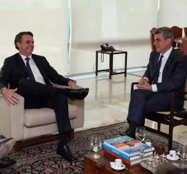 Jucá e Bolsonaro conversam sentados cada um em um sofá em Brasília