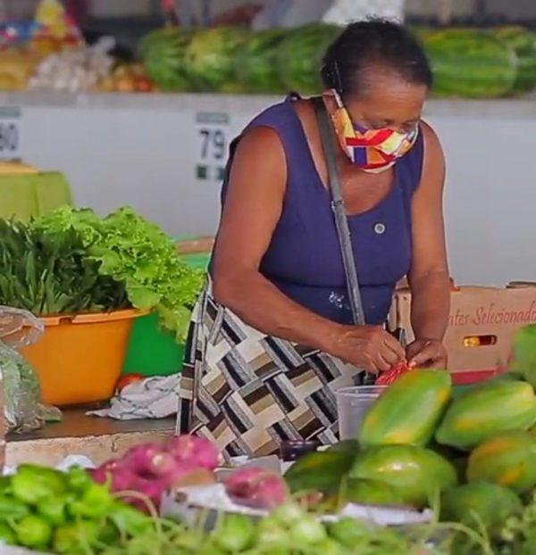Maria da Conceição mexendo nas frutas que vende