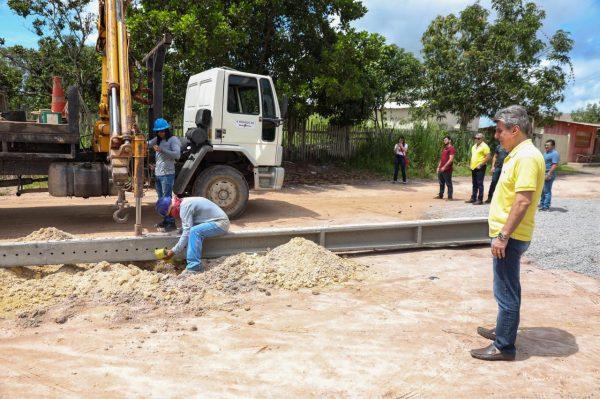 Romero Jucá olha homens colocando postes em Nova Colina