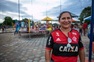 Hudislane Rodrigues usa a camisa do Flamengo e sorri com praça ao fundo