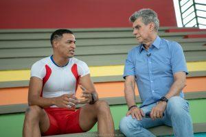 Romero Jucá e Deyvison Deluan sentados em arquibancada da Vila Olímpica. Falam sobre olímpiadas e apoio ao esporte