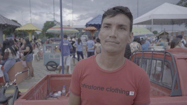 Wagner Vieira de camisa vermelha sorrindo. Ele vende chocolates na primeira Praça de Vista Alegre