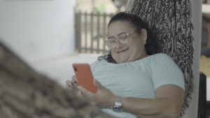 Clotilde Padilha, sentada em uma rede, sorri olhando para o celular e curtindo a estabilidade financeira adquirida