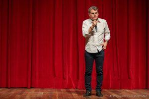 No Teatro Municipal, Romero Jucá fala sobre o Dia Nacional do Teatro. Ele veste roupa social e fala em frente da cortina vermelha do Teatro
