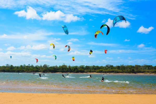 Pessoas praticando windsurf na praia do rio branco