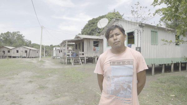 Thiago Marinho fala sobre o que tem no Baixo Rio Branco na Educação. Ele veste camiseta e está na frente de uma escola